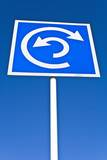 Roundabout sign over blue sky