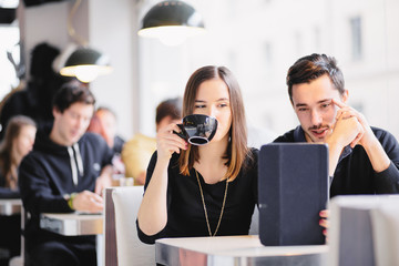 Couple looking at photos on tablet computer in cafe