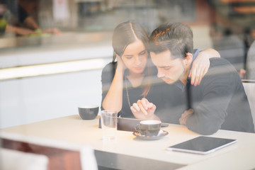 Couple using tablet computer in cafe