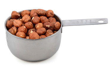Whole hazelnuts in a metal cup measure