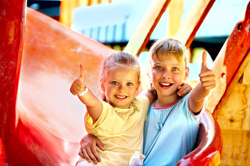 Children move out to slide in playground.