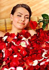 Beautiful young woman in rose petal swim water.