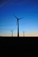 Trois éoliennes sous un ciel bleu nuit