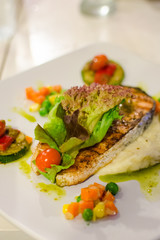 Grilled salmon steak with salad and parsley sauce