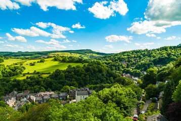 Bright sunny day view of green hills and village england