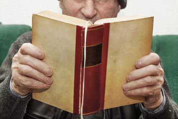 älterer Mann liest Buch