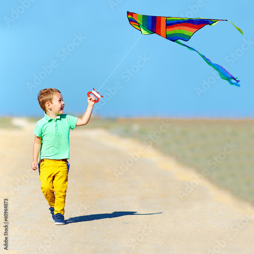 laughing boy playing with kite on summer field