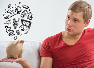 Handsome casual man with piggy bank in the living room at home