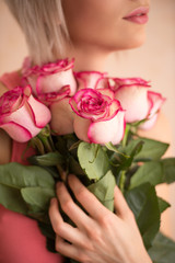 Unrecognizable woman holding bouquet of pink roses