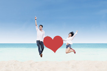 Asian couple jumping with heart card at beach