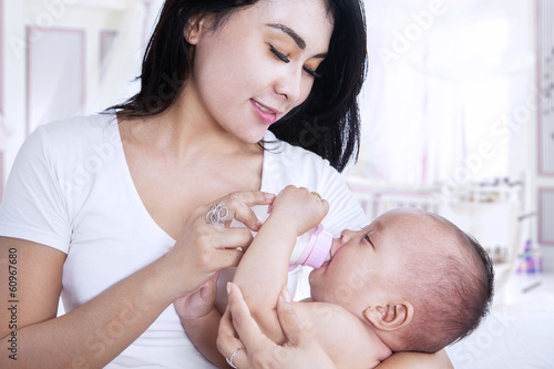 Attractive mother feeding her baby at home