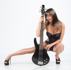 sexy  girl with a guitar. In a black swimsuit, bass