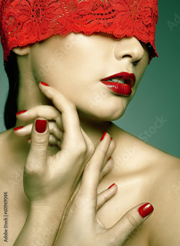 woman with red lacy ribbon on eyes