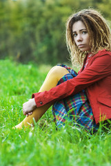 woman with dreadlocks sits grass