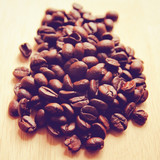 Coffee beans on wooden background with retro filter effect