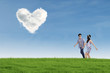 Romantic couple with heart shaped cloud in nature