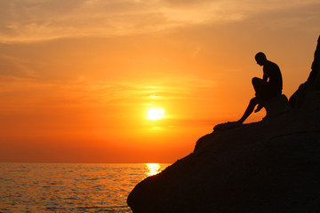 man on the cliff at sunset