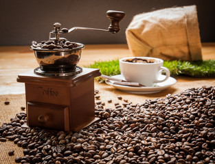 Coffee grinder beans and cup of coffee