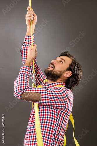 Young man trying to climb a rope-business concept-