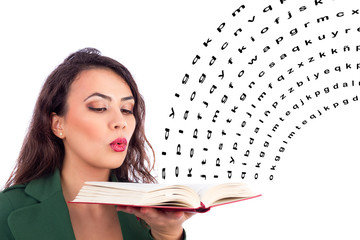 Beautiful young woman holding an open  book blowing on it