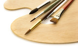 Art brushes on wooden palette isolated