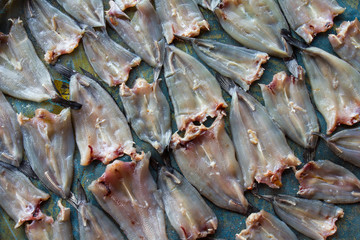 Thailand dried fish on the table paved with blue blinds