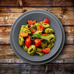ravioli di spinaci con pomodorini ed olive su legno