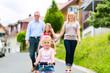 Familie macht Spaziergang durch Wohngebiet