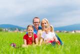 Glückliche Familie sitzt auf Wiese im Sommer