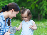 Cute little girl and her mother hugging little grey rabbit
