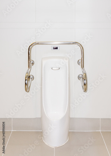 A male urinal with iron bar for accessibility in restroom