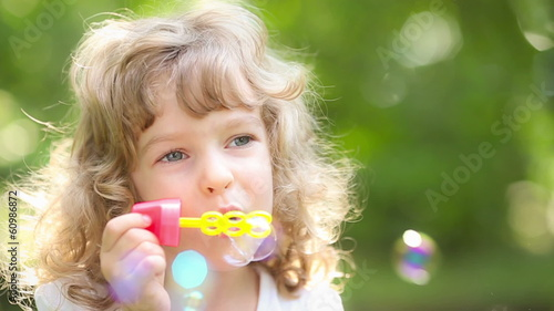 Happy child blowing soap bubbles outdoors in spring park