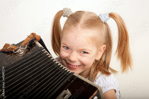 Smiling child with accordion. Little musician.