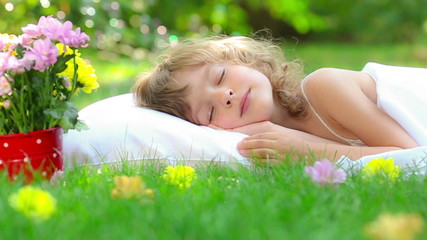 Happy child sleeping on green grass outdoors in spring garden