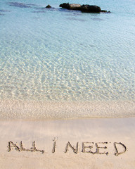 All I need message written on white sand