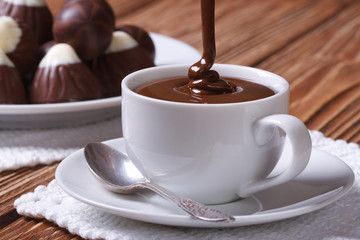 Chocolate is poured into a cup closeup on background sweets