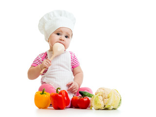 baby weared as cook with wooden spoon and vegetables