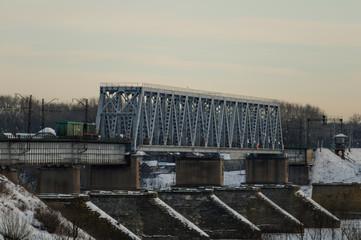 Diesel locomotive passing the railway bridge in winter