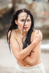 Frozen young woman on the cold sea beach