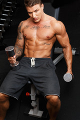 Muscled man wearing gray shorts holds barbells
