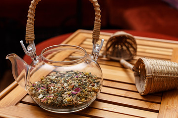 Glass teapot and two tea strainers on a red background