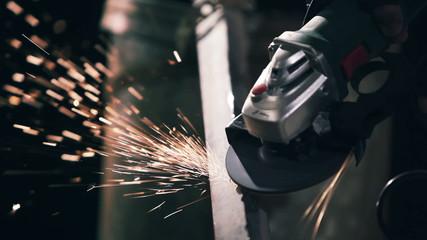 Manual sharpening. Sparks fly from metal grinder