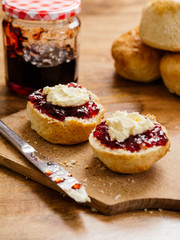 Two scones prepared with clotted cream and jam