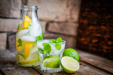 Water with lime,lemon and mint on rustic wooden table