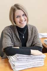 Cheerful woman with stack of paper documents in office