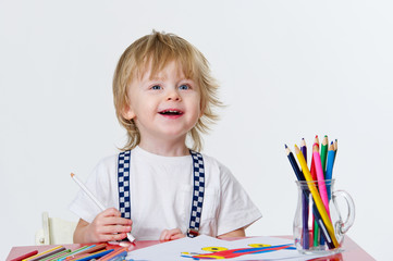 Cheerful kid drawing colorful paintings with bright pencils
