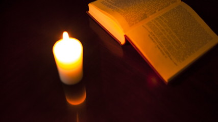 Book, hands, and candle