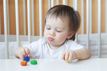 little boy age of 1 year with plasticine