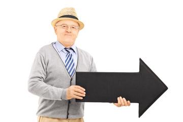 Senior gentleman holding big black arrow pointing right