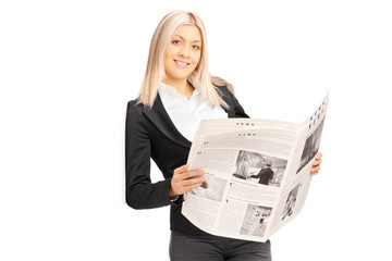 Young businesswoman holding newspaper and leaning against wall